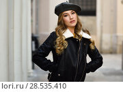 Купить «Blonde russian woman in urban background. Beautiful young girl wearing beret, black leather jacket and mini skirt standing in the street. Pretty female with long wavy hair hairstyle and blue eyes.», фото № 28535410, снято 24 января 2017 г. (c) Ingram Publishing / Фотобанк Лори