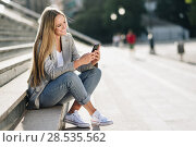 Beautiful young blonde woman looking at her smartphone and smiling. Стоковое фото, фотограф Javier Sánchez Mingorance / Ingram Publishing / Фотобанк Лори