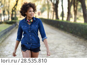 Купить «Young black woman with afro hairstyle walking in urban background. Mixed woman wearing blue shirt and shorts. Female carrying funny headphones.», фото № 28535810, снято 10 декабря 2016 г. (c) Ingram Publishing / Фотобанк Лори