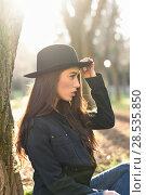 Купить «Portrait of thoughtful woman sitting alone outdoors wearing hat. Nice backlit with sunlight», фото № 28535850, снято 12 января 2016 г. (c) Ingram Publishing / Фотобанк Лори