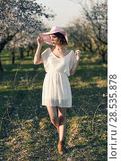 Portrait of young woman in the flowered field in the spring time. Almond flowers blossoms. Girl wearing white dress and pink sun hat. Стоковое фото, фотограф Javier Sánchez Mingorance / Ingram Publishing / Фотобанк Лори