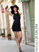 Купить «Brunette woman wearing black seductive dress and sun hat in the street. Young girl with curly hairstyle walking in urban background», фото № 28536994, снято 7 июля 2016 г. (c) Ingram Publishing / Фотобанк Лори