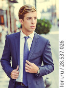 Купить «Portrait of an attractive young businessman in urban background wearing blue suit a necktie. Blonde hair», фото № 28537026, снято 17 сентября 2013 г. (c) Ingram Publishing / Фотобанк Лори