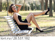 Купить «Portrait of funny woman, model of fashion with very long legs, sitting on a bench in an urban park, wearing black dress and high heels», фото № 28537182, снято 28 января 2015 г. (c) Ingram Publishing / Фотобанк Лори