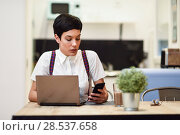 Купить «Young businesswoman with very short haircut looking at her smartphone at home.», фото № 28537658, снято 27 января 2018 г. (c) Ingram Publishing / Фотобанк Лори