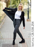 Купить «Funny blonde woman smiling in urban background. Young girl wearing black blazer jacket and striped trousers standing in the street. Pretty female with straight hair hairstyle and blue eyes.», фото № 28538254, снято 22 января 2017 г. (c) Ingram Publishing / Фотобанк Лори