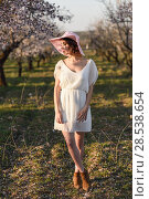 Купить «Portrait of young woman in the flowered field in the spring time. Almond flowers blossoms. Girl wearing white dress and pink sun hat», фото № 28538654, снято 10 марта 2015 г. (c) Ingram Publishing / Фотобанк Лори