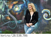 Купить «Funny blonde woman laughing in urban background. Young girl wearing black zipper jacket and blue jeans trousers standing in the street. Pretty female with straight hair hairstyle and blue eyes.», фото № 28538786, снято 22 января 2017 г. (c) Ingram Publishing / Фотобанк Лори