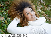 Купить «Beautiful young African American woman smiling with afro hairstyle and green eyes wearing white winter dress laying on the grass of an urban park», фото № 28538942, снято 25 ноября 2015 г. (c) Ingram Publishing / Фотобанк Лори