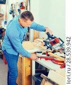 Купить «Woodworker male cutting wooden plank with fret saw in workplace», фото № 28539942, снято 17 мая 2017 г. (c) Яков Филимонов / Фотобанк Лори