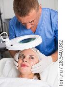 Купить «Man doctor is analysing skin on face of female patient before the procedure», фото № 28540082, снято 7 августа 2017 г. (c) Яков Филимонов / Фотобанк Лори