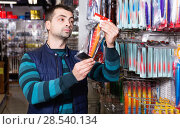 Купить «Man customer choosing fishing lures near stand in the sports shop», фото № 28540134, снято 16 января 2018 г. (c) Яков Филимонов / Фотобанк Лори