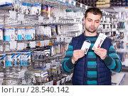 Купить «attentive male customer choosing fishing hooks near stand in the sports shop», фото № 28540142, снято 16 января 2018 г. (c) Яков Филимонов / Фотобанк Лори