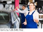 Купить «Female mechanic welcoming in car workshop», фото № 28540162, снято 4 апреля 2018 г. (c) Яков Филимонов / Фотобанк Лори
