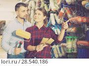 Купить «Young female and man choosing brushes and roller», фото № 28540186, снято 16 февраля 2018 г. (c) Яков Филимонов / Фотобанк Лори