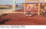 Купить «The red-haired girl rides on a self-balancing scooter. Children on the playground», видеоролик № 28542770, снято 2 декабря 2017 г. (c) Олег Хархан / Фотобанк Лори