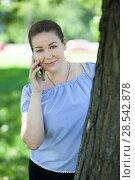 Купить «Девушка с мобильным телефоном в парке возле дерева», фото № 28542878, снято 3 июня 2018 г. (c) Кекяляйнен Андрей / Фотобанк Лори