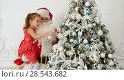 Купить «Santa Claus with pretty little girl decorating Christmas tree», фото № 28543682, снято 21 ноября 2019 г. (c) Vasily Alexandrovich Gronskiy / Фотобанк Лори