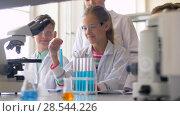 Купить «teacher and students studying chemistry at school», видеоролик № 28544226, снято 28 мая 2018 г. (c) Syda Productions / Фотобанк Лори