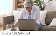 Купить «senior woman with laptop and calculator at home», видеоролик № 28544334, снято 30 мая 2018 г. (c) Syda Productions / Фотобанк Лори