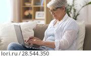 Купить «happy senior woman typing on laptop at home», видеоролик № 28544350, снято 29 мая 2018 г. (c) Syda Productions / Фотобанк Лори