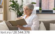 Купить «senior woman writing to notebook or diary at home», видеоролик № 28544378, снято 29 мая 2018 г. (c) Syda Productions / Фотобанк Лори