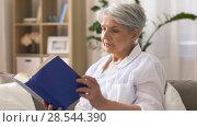 Купить «senior woman reading book at home», видеоролик № 28544390, снято 29 мая 2018 г. (c) Syda Productions / Фотобанк Лори