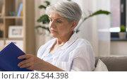 Купить «senior woman reading book at home», видеоролик № 28544398, снято 29 мая 2018 г. (c) Syda Productions / Фотобанк Лори