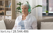 Купить «senior woman in headphones listening to music», видеоролик № 28544486, снято 29 мая 2018 г. (c) Syda Productions / Фотобанк Лори