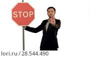 Купить «A businessman holding a stop sign on laptop on white background isolated.», фото № 28544490, снято 21 февраля 2019 г. (c) Vasily Alexandrovich Gronskiy / Фотобанк Лори