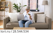 Купить «senior woman with laptop and credit card at home», видеоролик № 28544534, снято 29 мая 2018 г. (c) Syda Productions / Фотобанк Лори