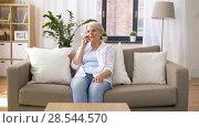 Купить «senior woman calling on smartphone at home», видеоролик № 28544570, снято 29 мая 2018 г. (c) Syda Productions / Фотобанк Лори