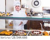 Купить «Portrait of middle aged man baker with tasty cakes smiling in bakery», фото № 28544666, снято 22 апреля 2017 г. (c) Яков Филимонов / Фотобанк Лори