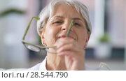 Купить «portrait of happy senior woman in glasses», видеоролик № 28544790, снято 30 мая 2018 г. (c) Syda Productions / Фотобанк Лори