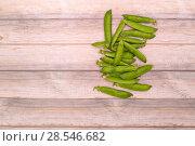 Купить «Стручки зелёного горошка на деревянном фоне», фото № 28546682, снято 4 июня 2018 г. (c) V.Ivantsov / Фотобанк Лори