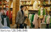 Купить «Couple is satisfied shopping and walking with package in the clothes store.», видеоролик № 28546846, снято 27 марта 2018 г. (c) Яков Филимонов / Фотобанк Лори