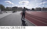 Купить «Electric Longboard summer ride on red sport stadium with playground», видеоролик № 28554518, снято 10 июня 2018 г. (c) Aleksejs Bergmanis / Фотобанк Лори