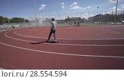 Купить «Electric Longboard summer ride on red sport stadium with playground», видеоролик № 28554594, снято 9 июня 2018 г. (c) Aleksejs Bergmanis / Фотобанк Лори