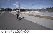 Купить «Electric Longboard summer ride on red sport stadium with playground», видеоролик № 28554650, снято 10 июня 2018 г. (c) Aleksejs Bergmanis / Фотобанк Лори
