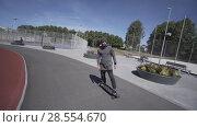 Купить «Electric Longboard man in sweatshirt and hat ride on red sport stadium with playground», видеоролик № 28554670, снято 10 июня 2018 г. (c) Aleksejs Bergmanis / Фотобанк Лори