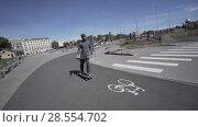 Купить «Electric Longboard man in sweatshirt and hat ride on red sport stadium with playground», видеоролик № 28554702, снято 9 июня 2018 г. (c) Aleksejs Bergmanis / Фотобанк Лори