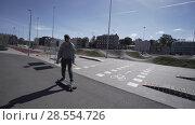 Купить «Electric Longboard man in green shirt and hat ride on red sport stadium with playground», видеоролик № 28554726, снято 10 июня 2018 г. (c) Aleksejs Bergmanis / Фотобанк Лори