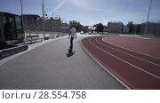 Купить «Electric Longboard man in white t-shirt and hat ride on red sport stadium with playground», видеоролик № 28554758, снято 9 июня 2018 г. (c) Aleksejs Bergmanis / Фотобанк Лори