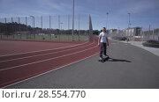 Купить «Electric Longboard man in white t-shirt and hat ride on red sport stadium with playground», видеоролик № 28554770, снято 9 июня 2018 г. (c) Aleksejs Bergmanis / Фотобанк Лори