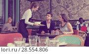 Купить «Waitress bringing dishes to couple», фото № 28554806, снято 7 марта 2018 г. (c) Яков Филимонов / Фотобанк Лори