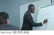 Купить «Afro-american businessman making presentation of a business plan on the flipchart», видеоролик № 28555426, снято 11 мая 2017 г. (c) Vasily Alexandrovich Gronskiy / Фотобанк Лори