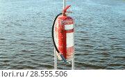 Купить «Огнетушитель на фоне воды в солнечный день», видеоролик № 28555506, снято 10 июня 2018 г. (c) FMRU / Фотобанк Лори
