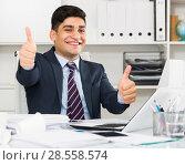 Купить «Male employee is having productive day at work», фото № 28558574, снято 18 мая 2017 г. (c) Яков Филимонов / Фотобанк Лори
