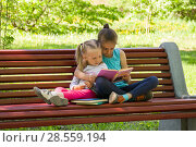 Купить «Дети сидят на скамейке в парке и увлеченно читают книгу», фото № 28559194, снято 29 мая 2018 г. (c) Лариса Капусткина / Фотобанк Лори