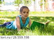 Купить «Девочка лежит на траве в парке с раскрытой книгой в руках», фото № 28559198, снято 29 мая 2018 г. (c) Лариса Капусткина / Фотобанк Лори